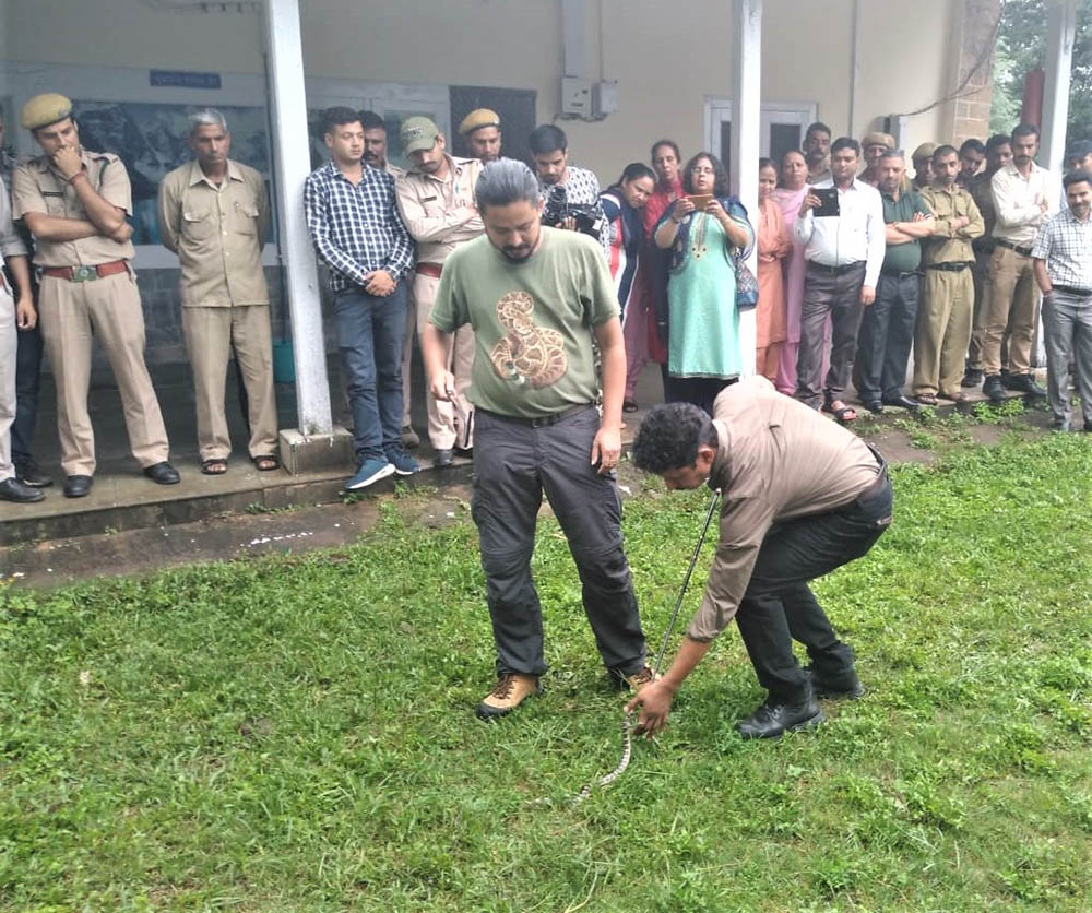 Vishal Santra (Simultala Conservationists) trains the Dharamsala Divisional Forest Officer, Shri Dadwal,  in the use of snake handling equipment